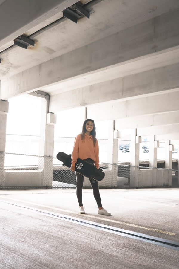 natalie pluto chilling in a parking garage with her longboard
